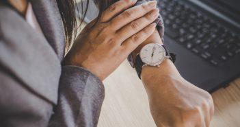 Blick auf Armbanduhr vor Laptop Vollzeit arbeiten
