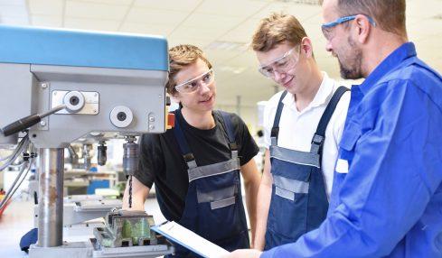 Auszubildende zum Werkzeugmechaniker stehen mit Ausbilder an einer Maschinne