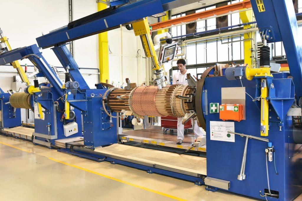Junger Industriemechaniker in Fabrikhalle an riesiger Kupferdrahtrolle