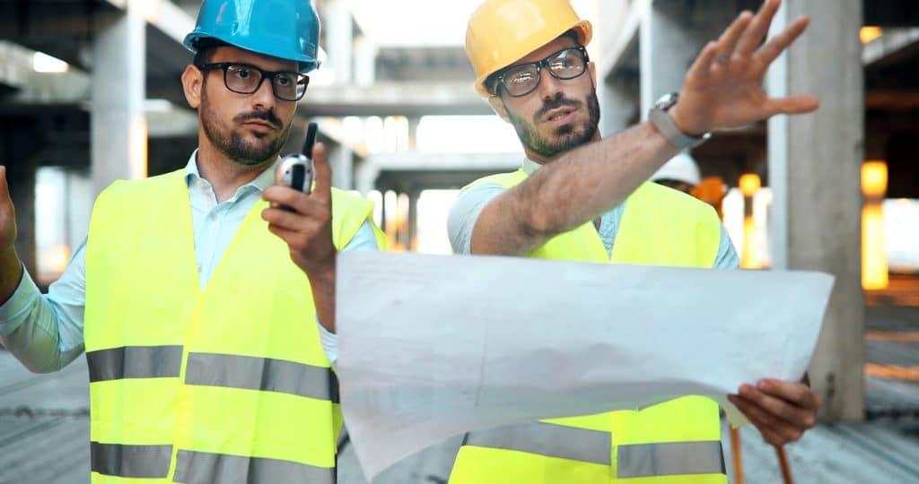 Zwei Bauingenieure mit Plan im Fachgespräch auf der Baustelle