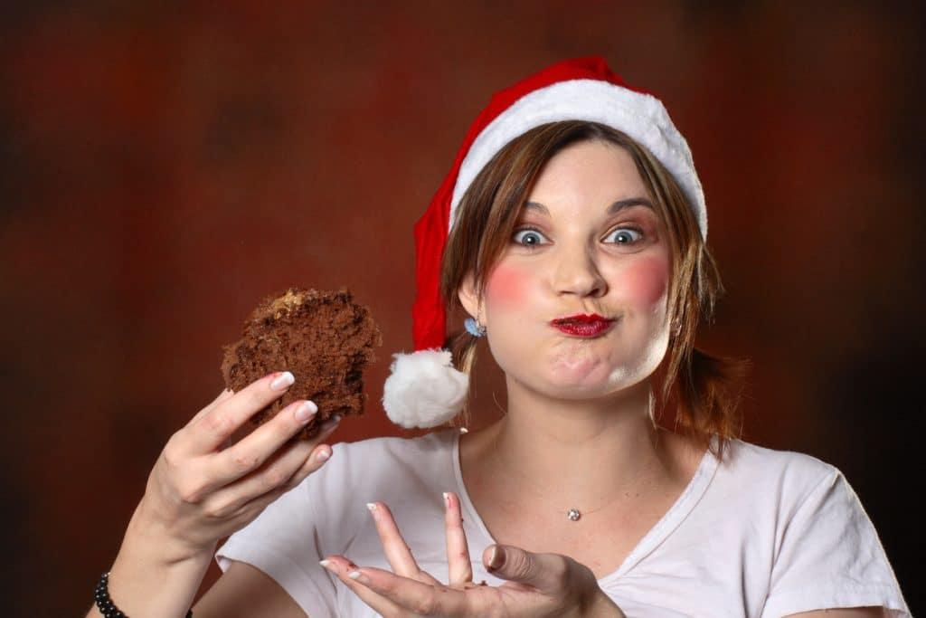 Jobs für Weihnachtsfreaks Frau mit Nikolausmütze beißt ihn Kuchen
