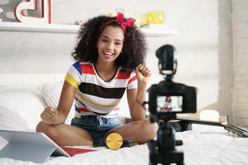 Junge Influencerin sitzt auf Bett vor Kamera
