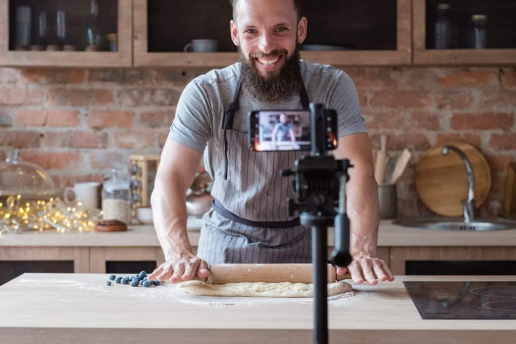 Influencer bzw. Food Blogger rollt vor Kamera Teig aus