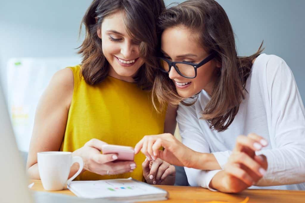 Arbeitskolleginnen schauen sich etwas auf dem Smartphone an