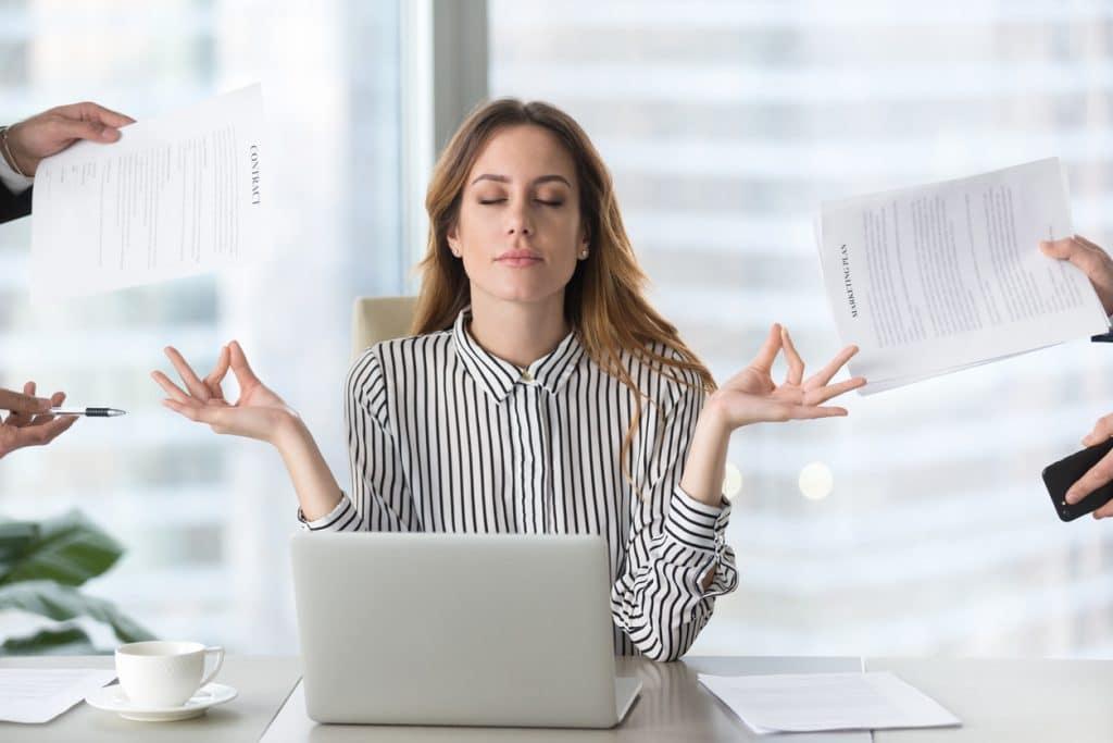 Junge Frau meditiert an Schreibtisch im Büro
