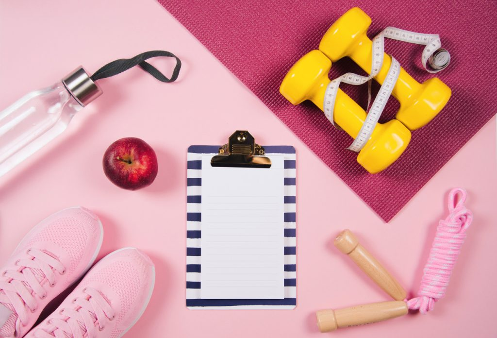 Fitnessgeräte auf rosa Matte