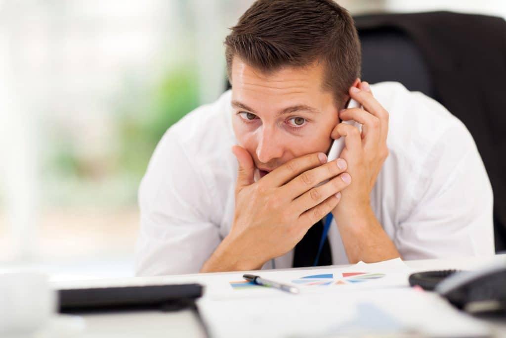 Mitarbeiter am Arbeitsplatz führt Privatgespräch mit Handy
